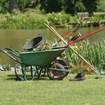 A variety of gardening tools with a pond in the background
